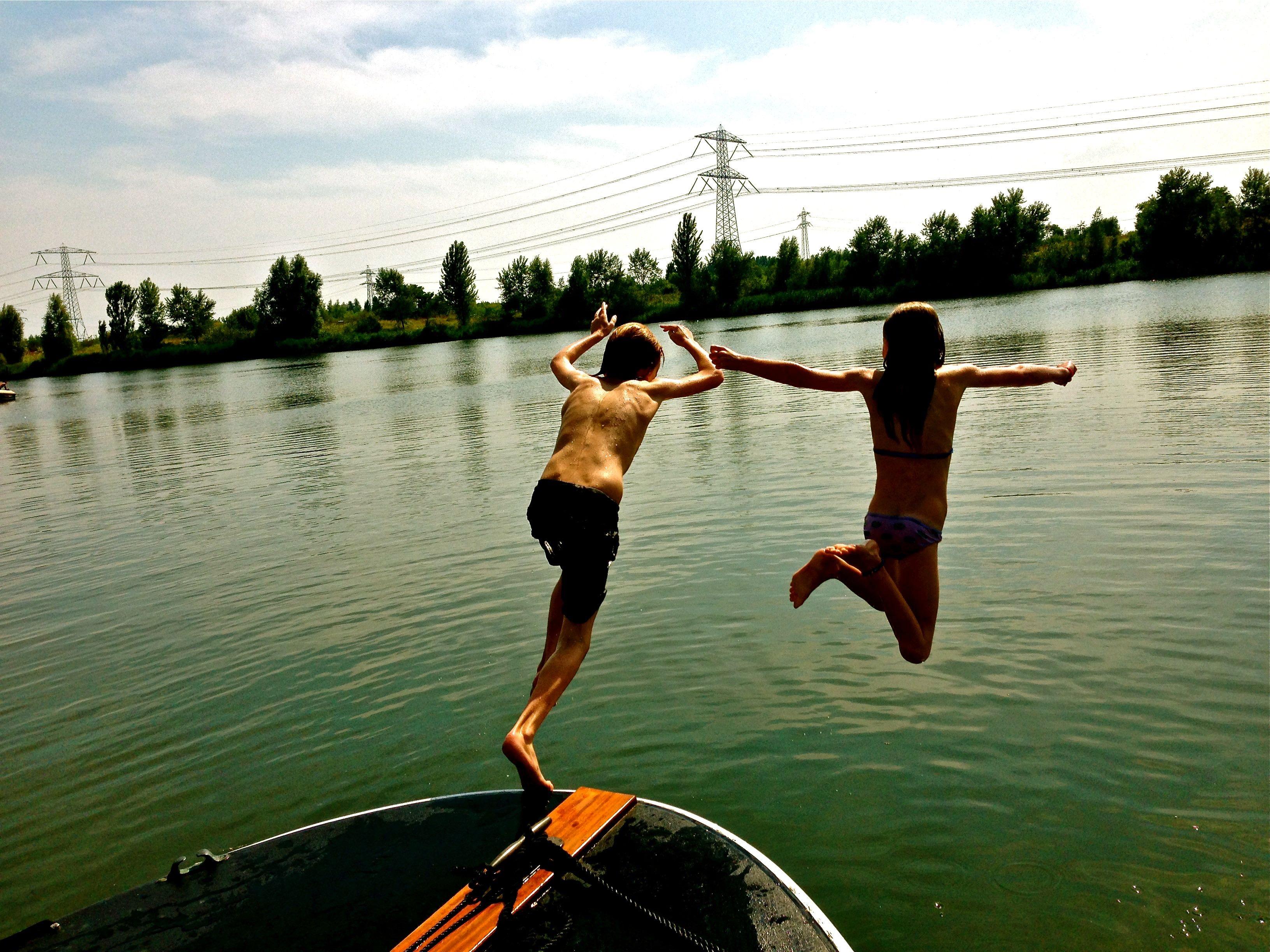 kinderen duiken het water in vanaf bootje